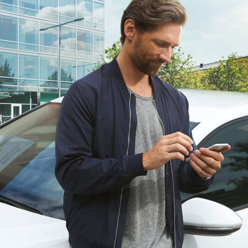 Man on his phone in front of a Volkswagen retailer