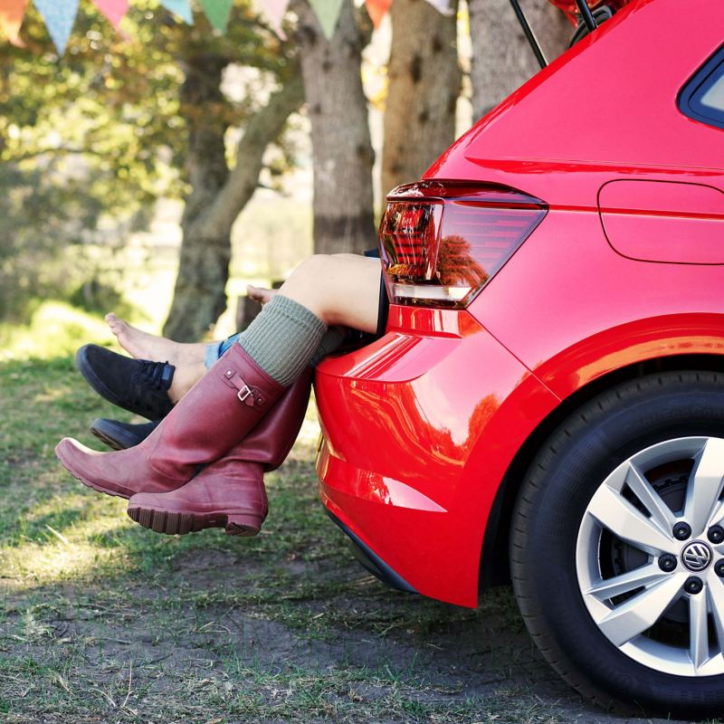 Boots hanging down from the back of the a red Volkswagen Polo at a festival.