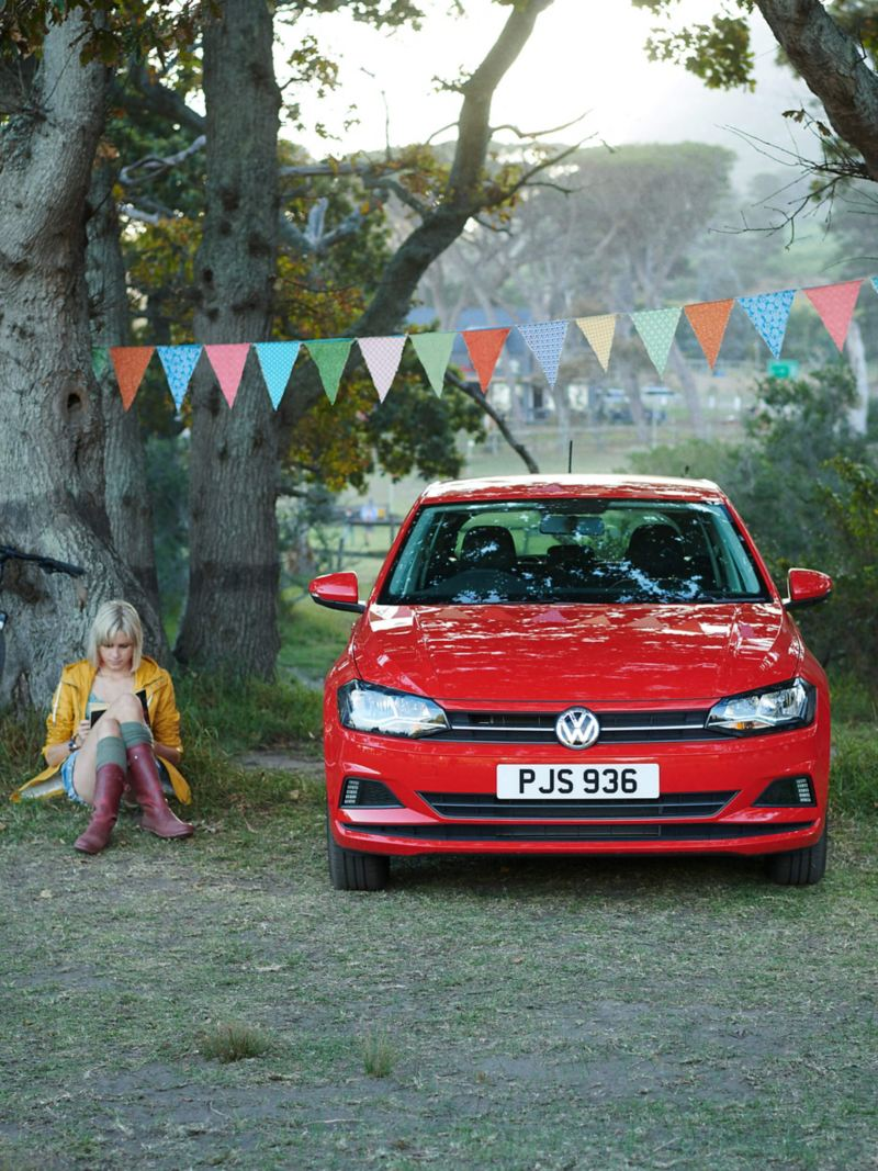 Woman reading at a festival by a red Volkswagen Polo, surrounded by trees and bunting.