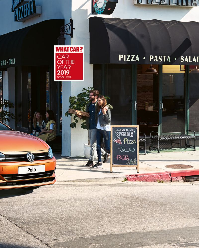 A orange Volkswagen Polo turning a street corner, past a busy bistro, the coast visible in the background.
