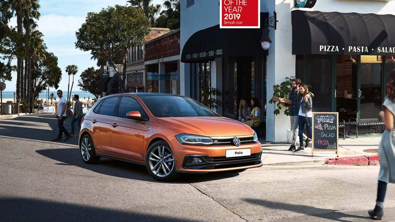 An orange Volkswagen Polo turning a street corner, past a busy coastal pizzeria.