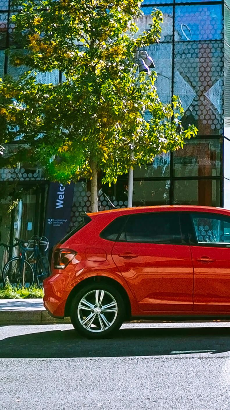 A red Volkswagen Polo parked outside a building.