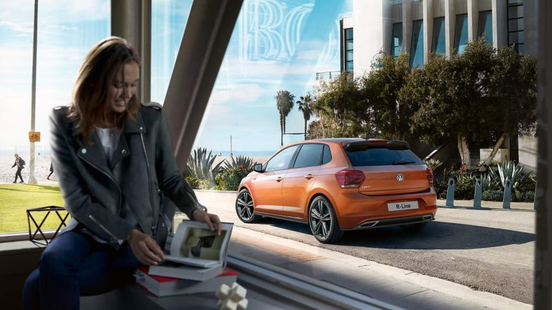 A orange Polo R-Line, driving to the beach, past a lady in cafe window reading a book.