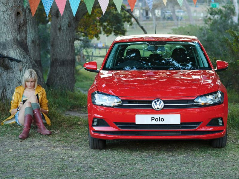 A woman sits next to a red Polo