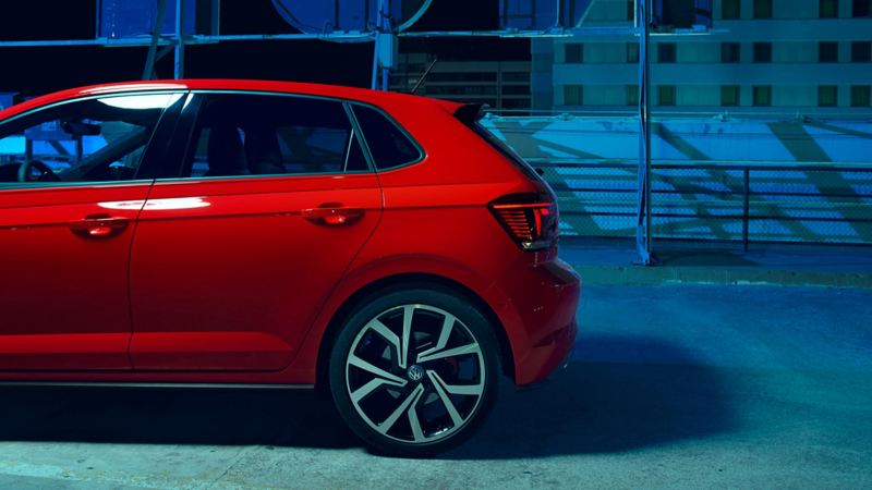 Back profile shot of a red Volkswagen Polo at night.