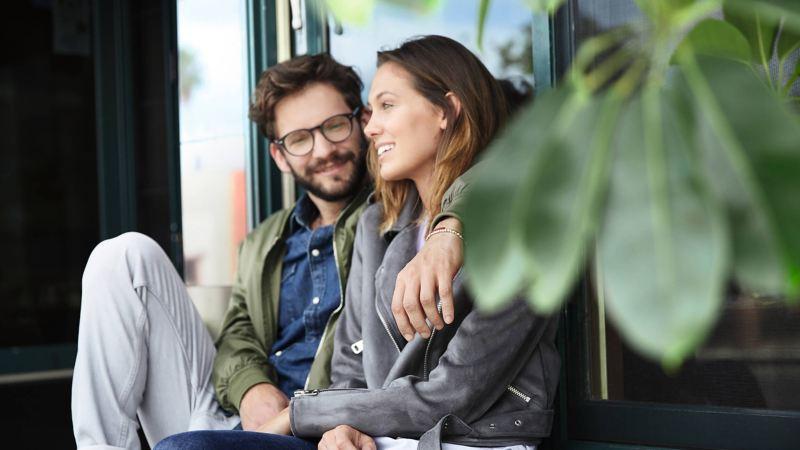 A couple smiling outside a shopfront.