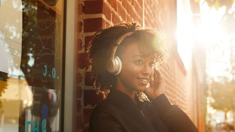 Woman with Beats headphones outside a record shop, the sun setting behind her.