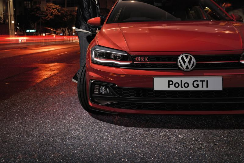 Volkswagen Polo GTI font view with the city at night, blurred in the background.