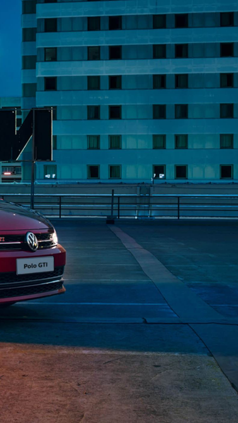 A red Volkswagen Polo GTI parked on top of a city tower at night.