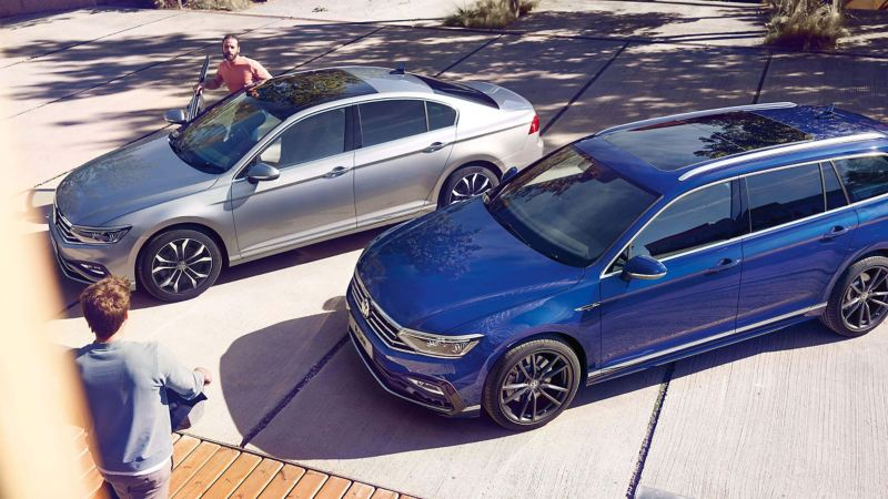 A silver Volkswagen Arteon Saloon and a Blue Volkswagen Passat Estate , side by side.