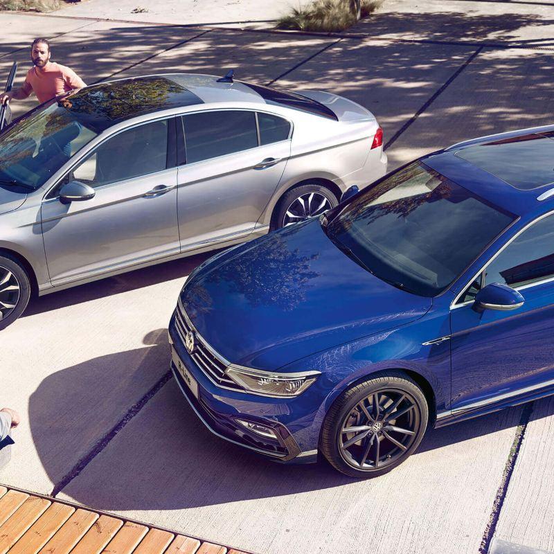 A silver Volkswagen Arteon Saloon and a Blue Volkswagen Passat Estate , side by side.