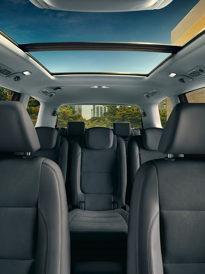 Interior shot of a Sharan focusing on the leather seats and panoramic glass roof.