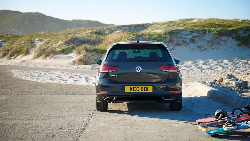 A black Volkswagen Golf next on the beach, next to sand-dunes.