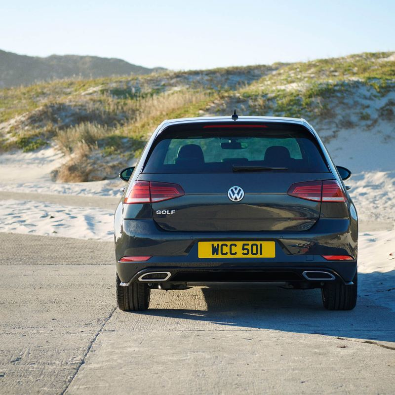 A black Volkswagen Golf next on the beach, next to sand-dunes.