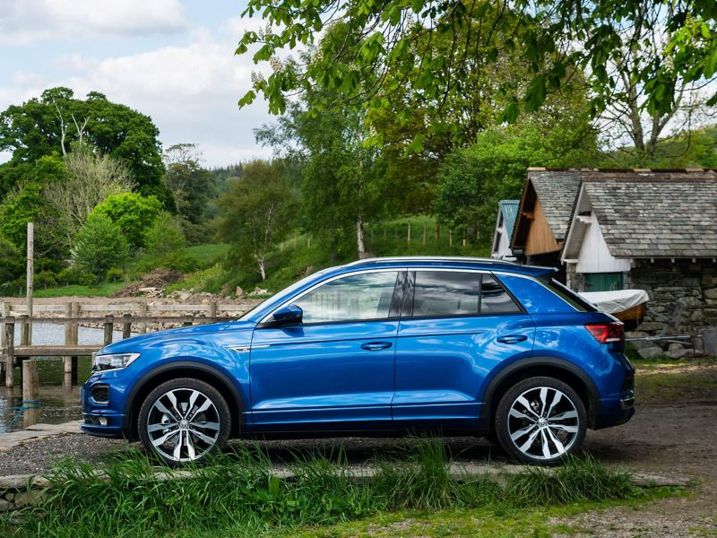A blue Volkswagen T-Roc next to a lake and countryside cabins.