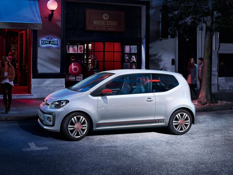 A white Volkswagen up! parked on a well-lit city street at night.