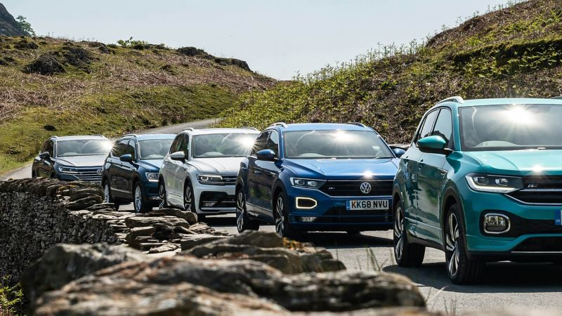 The Volkswagen SUV range, a T-Cross, a T-Roc, a Tiguan, a Tiguan Allspace, and a Touareg parking in the mountains.
