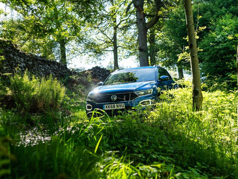 A blue Volkswagen T-Roc in the countryside