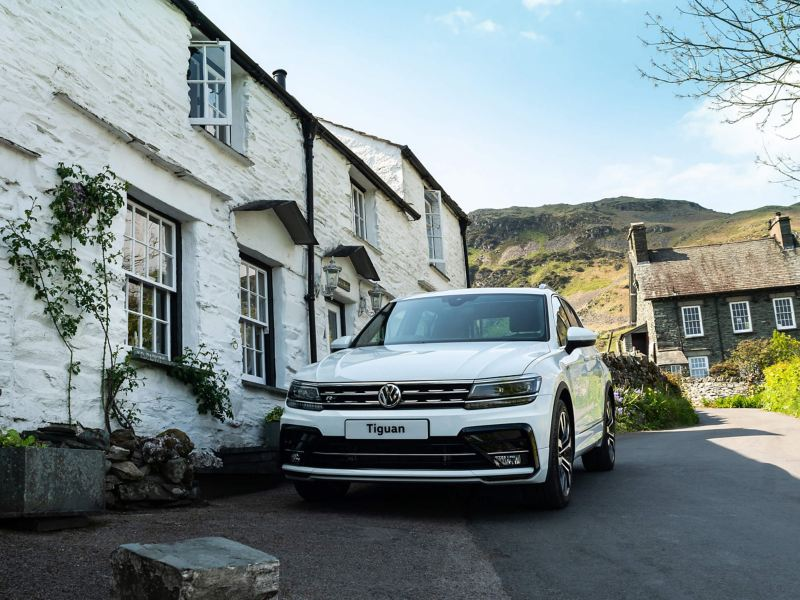 A Volkswagen Tiguan parked outside a building in the countryside