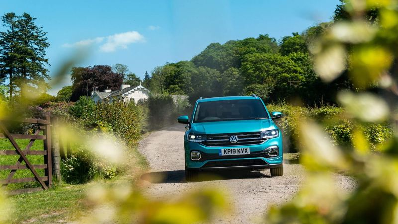 Green Volkswagen T-Cross on a country lane