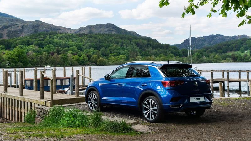 A blue Volkswagen T-Roc parked by a lake
