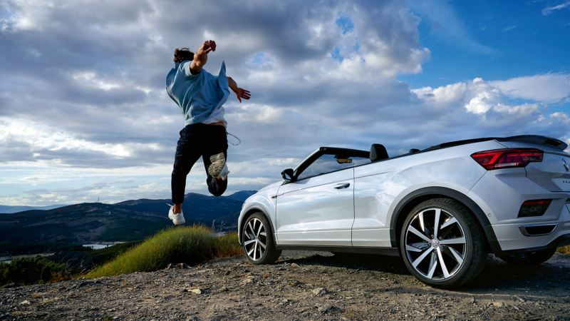 A white Volkswagen T-Roc Cabriolet parked with a man jumping next to it