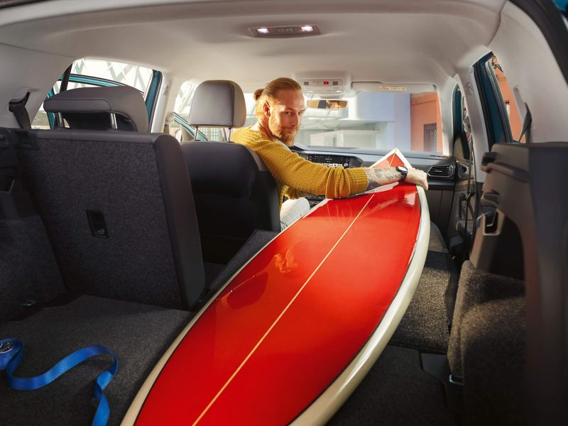 Interior shot of a man in a Volkswagen T-Cross with the seats folded down