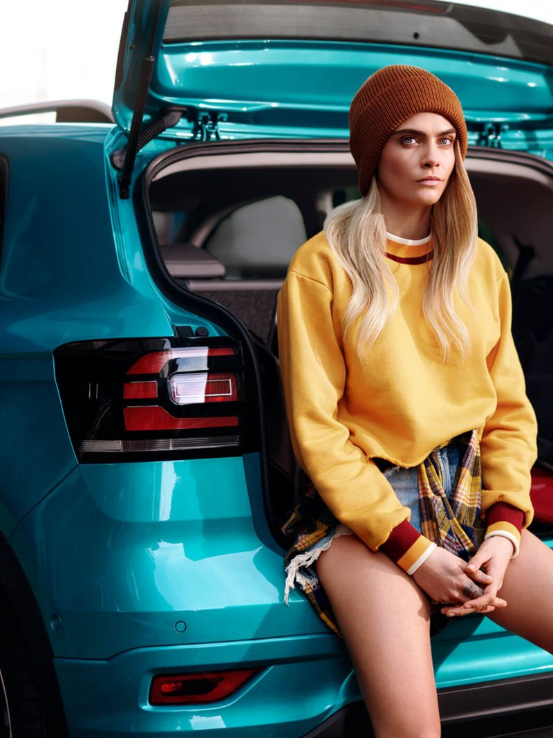 Shot of Cara Delevingne sitting in the boot of a Volkswagen R-Line