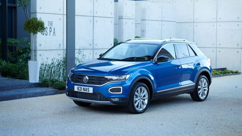 3/4 front shot of a blue Volkswagen T-Roc parked in front of a spa.