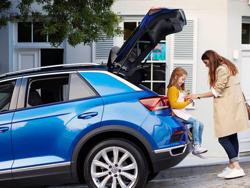 A young girl sat in the open boot of a blue Volkswagen T-Roc, with her mother.