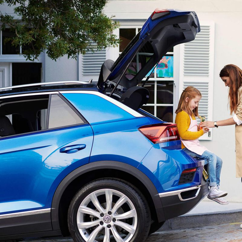 Girl sitting on the boot of a blue Volkswagen T-Roc, her mother giving her a drink.