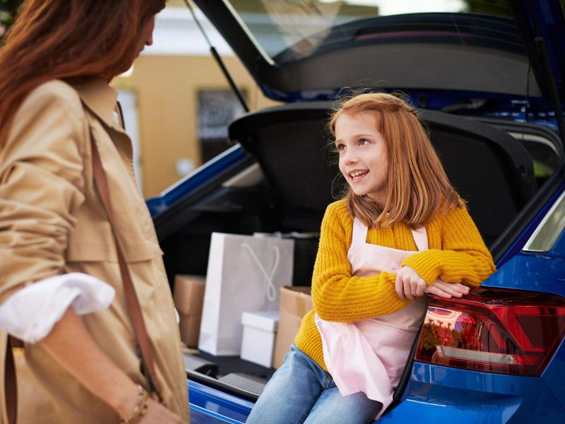 Girl sitting in the boot of a Volkswagen, with shopping.