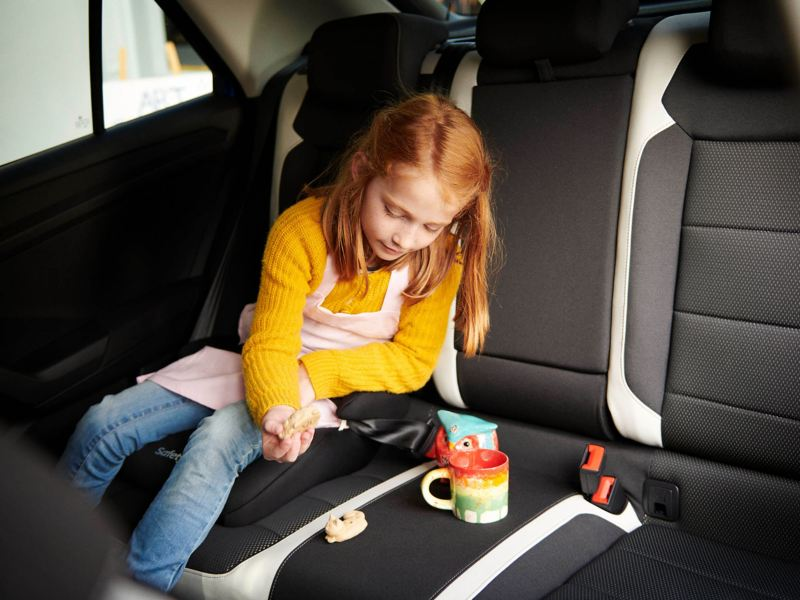 Girl sitting in the back of a Volkswagen car