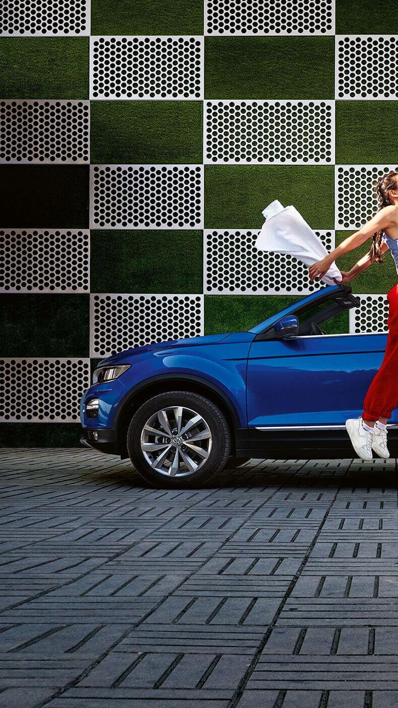 A woman jumping near a blue Volkswagen T-Roc Cabriolet