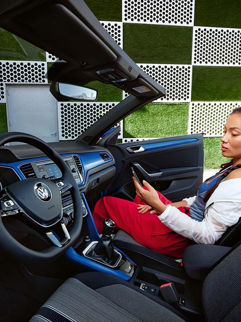 A lady using her phone inside the T-Roc Cabriolet