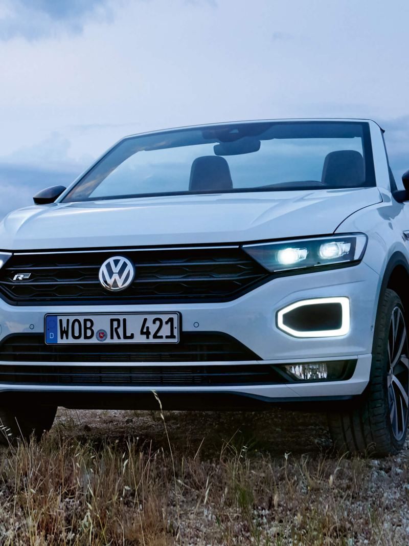 A white Volkswagen T-Roc Cabriolet parked in the mountains