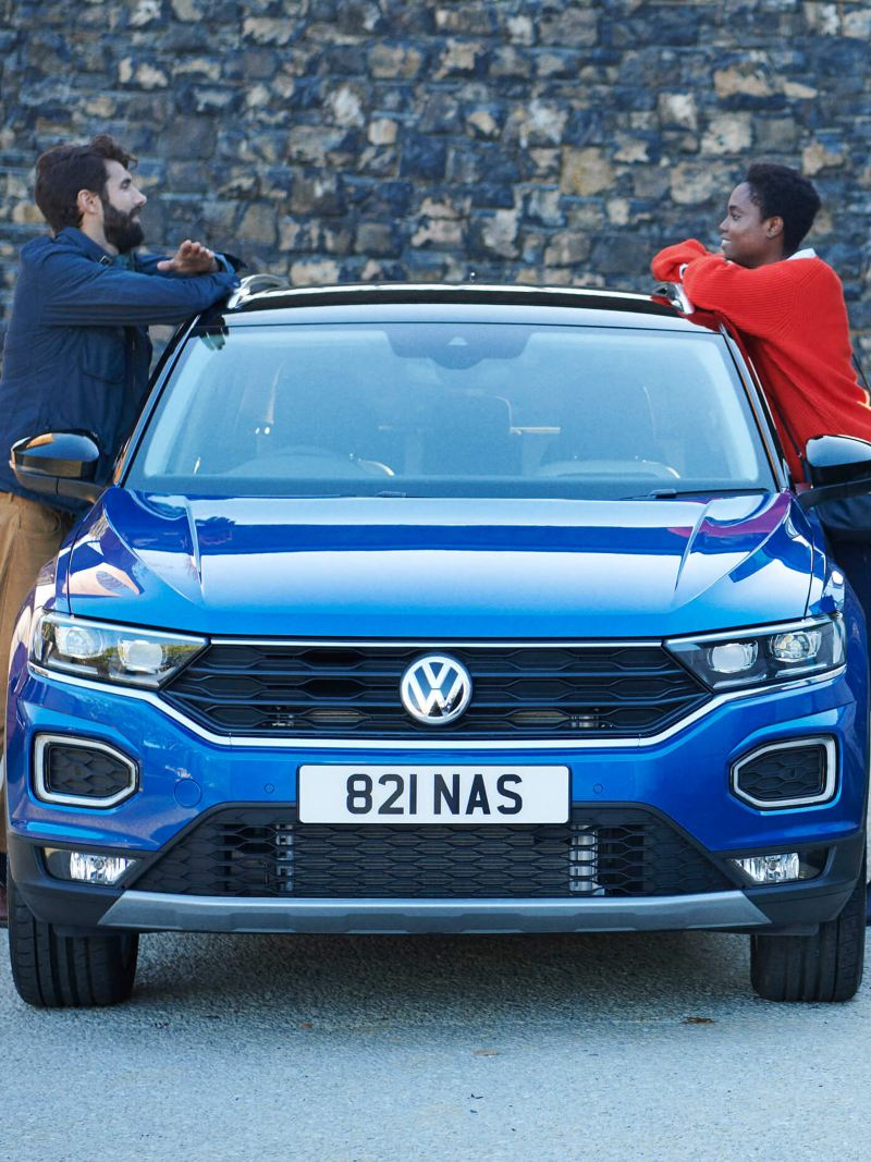 A blue Volkswagen T-Roc with a couple