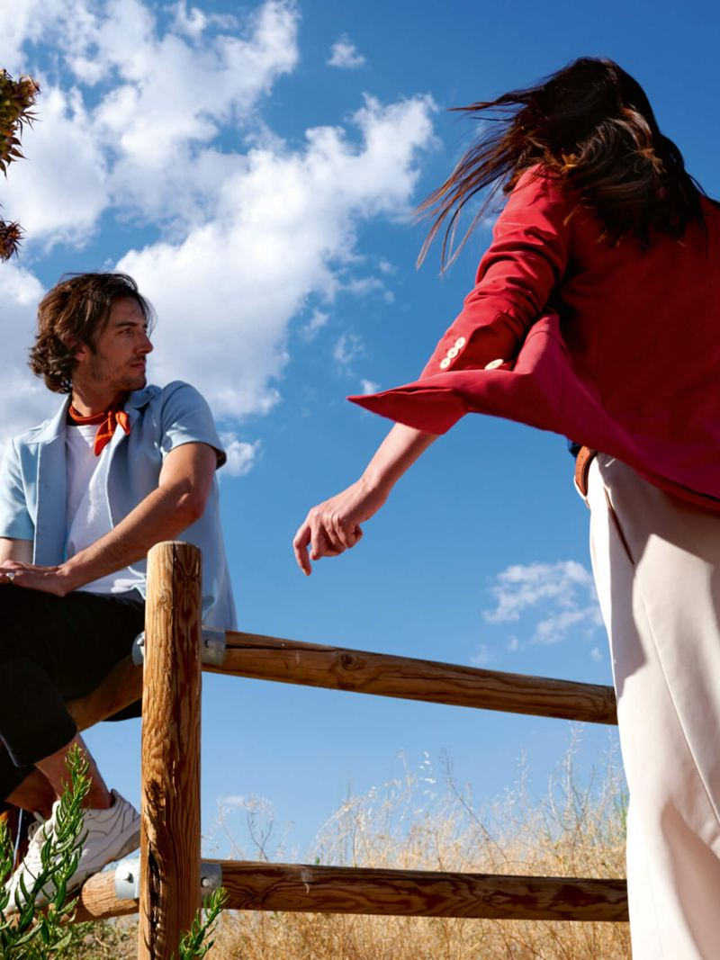 A woman walking towards a man who is sitting on a fence