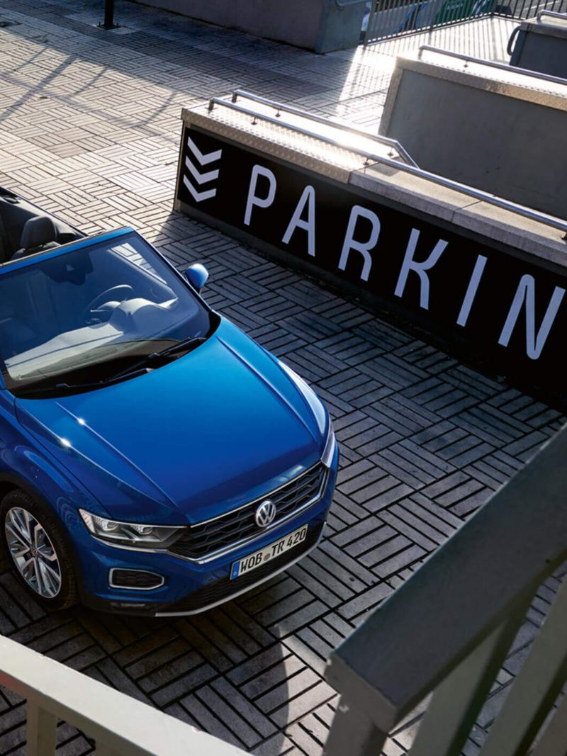 A woman in front of a blue Volkswagen T-Roc Cabriolet