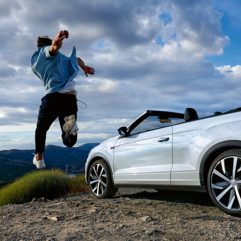 A man jumping near his white Volkswagen T-Roc Cabriolet