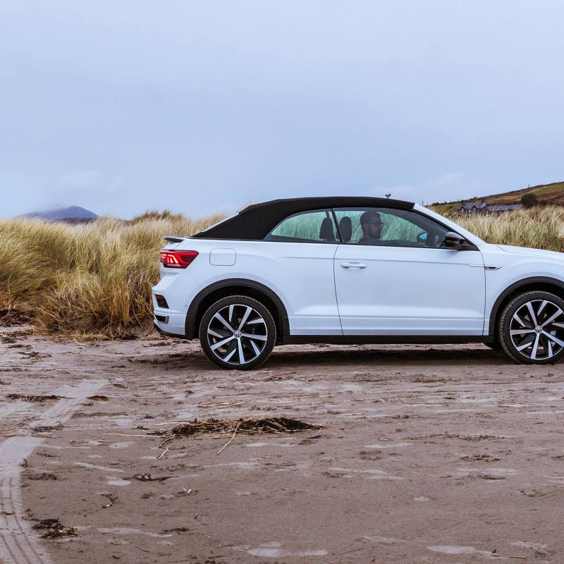 A man sitting in a white T-Roc Cabriolet on the beach