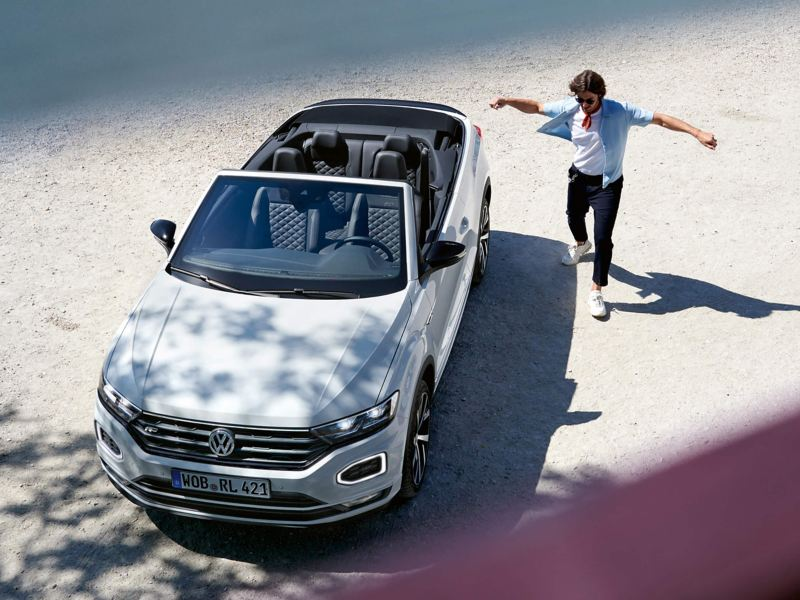 Man jumping next to a T-Roc Cabriolet car