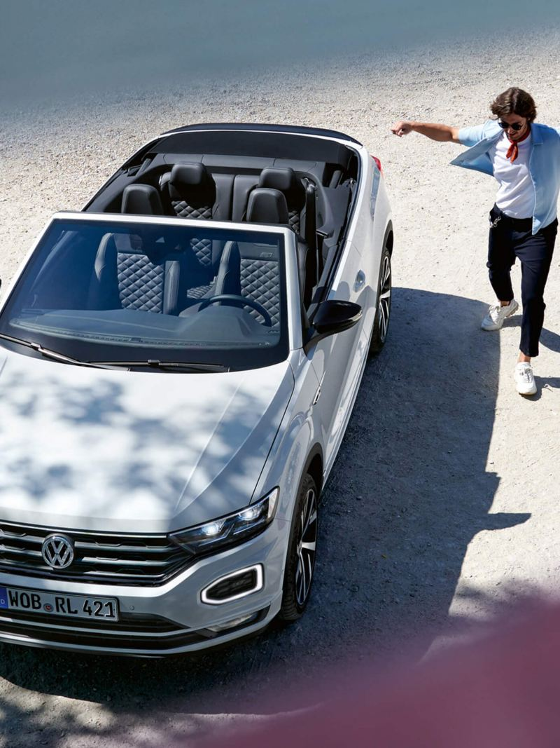 A man dancing near his Volkswagen T-Roc Cabriolet on the beach