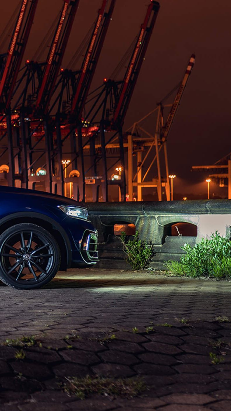 A blue T-Roc R in the night, at the docking yard of a city.
