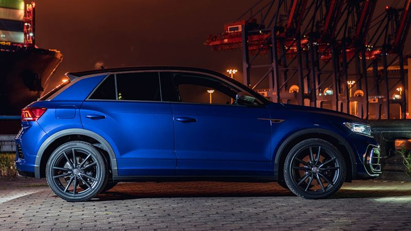 A blue Volkswagen T-Roc R from profile, at the dock yard of a city.