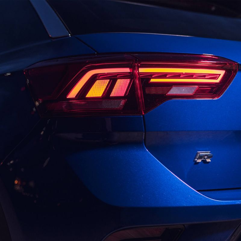 The rear light of a blue Volkswagen T-Roc R and the R badge