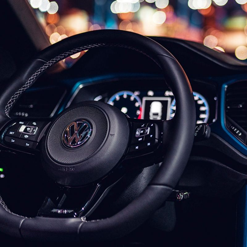 The interior of a Volkswagen T-Roc R showing the steering wheel, the dahsboard and the centre console