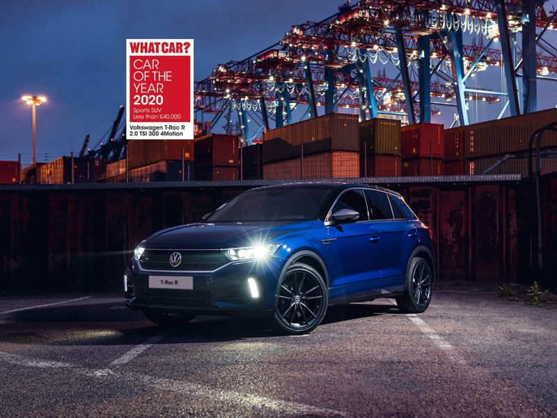 A blue Volkswagen T-Roc R parked in the night,  at the docking yard of a city.
