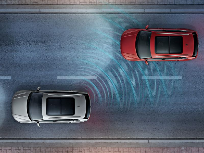 A red Volkswagen Tiguan is overtaking a silver Volkswagen Tiguan which has the Lane Assist on
