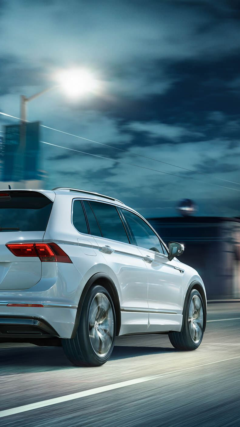 White Volkswagen Tiguan R-Line, driving down a city street at night.